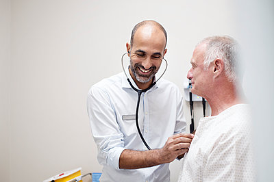Smiling doctor checking patient's heartbeats - p1166m1226190 by Cavan Images