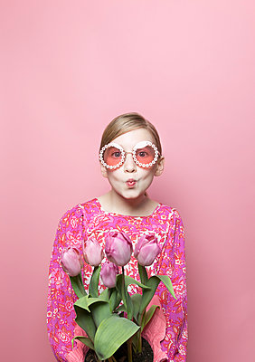 Mod blonde tween girl, blue eyes, pink background, pink floral dress - p1166m2171545 by Cavan Images