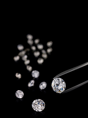 Tweezers and cut diamonds against black background - p3007423f by Andreas Koschate