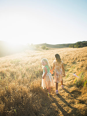 Caucasian girls holding hands in rural field - p555m1463791 by Erik Isakson