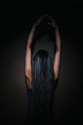 Junge Frau mit langen dunklen Haaren posiert, Rückansicht - p586m953776 von Kniel Synnatzschke