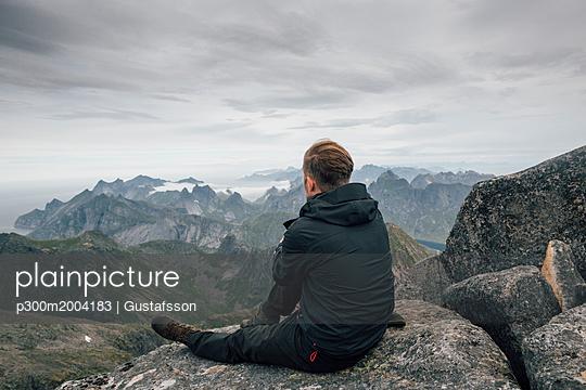 Norway, Lofoten, Moskenesoy, Young man sitting at Hermannsdalstinden, looking over Kjerkefjord - p300m2004183 von Gustafsson
