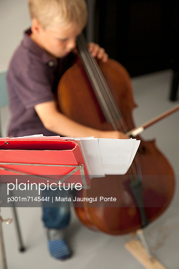 Boy playing cello with sheet music in the foreground - p301m714544f by Maria Jauregui Ponte