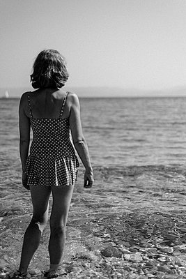 Back of female in polka dot swimsuit on pebbly beach. - p1433m1526039 by Wolf Kettler