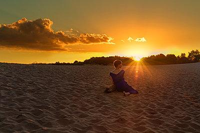 Frau sitzt im Sand und schaut in den Sonnenuntergang - p1491m2100733 von Jessica Prautzsch