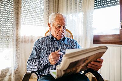 Senior man reading newspaper at home - p300m1113532f by Josep Rovirosa