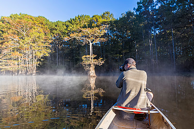 USA, Texas, Louisiana, Caddo Lake, bald cypress forest, tourist with camera in kayak - p300m1449365 by Fotofeeling