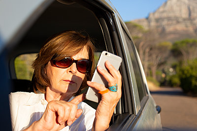 Senior woman using smartphone in a car - p975m2063286 by Hayden Verry