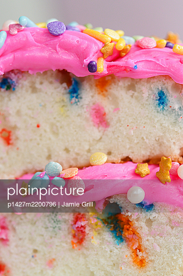 Colorful sprinkles on pink cake frosting - p1427m2200796 by Jamie Grill