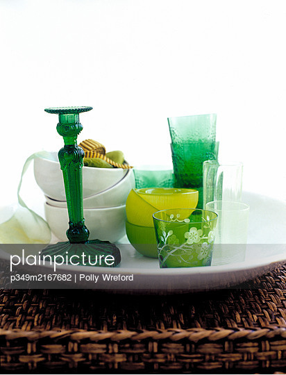 Green glassware and bowls on wicker tray. - p349m2167682 by Polly Wreford