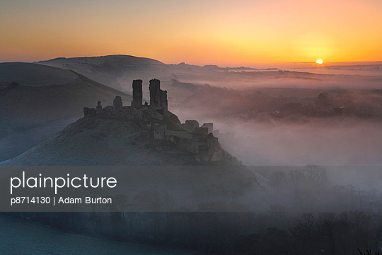 Mist surrounds the ruins of Corfe Castle at sunrise - p8714130 by Adam Burton
