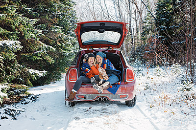 Cheerful female friends sitting in car trunk at Algonquin Provincial Park during winter - p1166m1577898 by Cavan Images