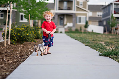 Portrait of cute baby boy with puppy standing on footpath in park - p1166m2067851 by Cavan Images