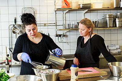 Women preparing food in restaurant kitchen - p312m2237109 by Phia Bergdahl
