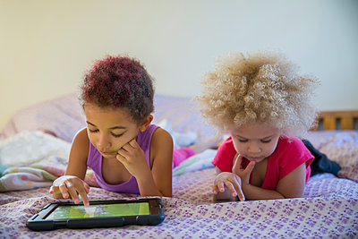 Mixed race sisters using digital tablets in bed - p555m1419536 by Inti St Clair photography