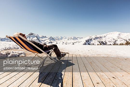 Austria, Damuels, senior man relaxing in deckchair on sun deck in winter landscape - p300m1505584 by Nullplus