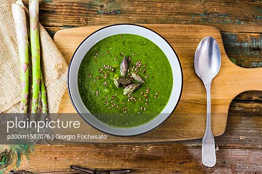 Fresh green asparagus, asparagus soup in bowl - p300m1587076 von Giorgio Fochesato