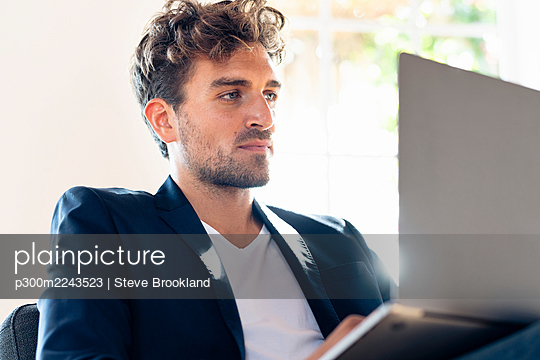 Businessman working on laptop while sitting at home - p300m2243523 by Steve Brookland
