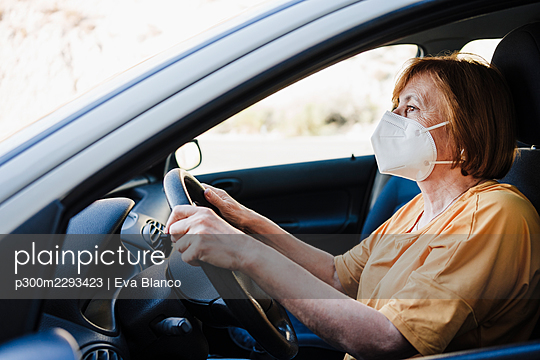 Woman wearing protective face mask while driving car during COVID-19 - p300m2293423 by Eva Blanco