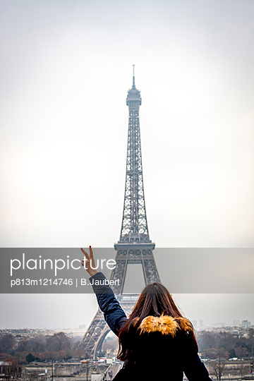 Young woman making the sign of victory in front of the Eiffel Tower - p813m1214746 by B.Jaubert