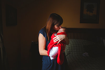 Mother kissing cute daughter while carrying her in bedroom at home - p1166m2112443 by Cavan Images