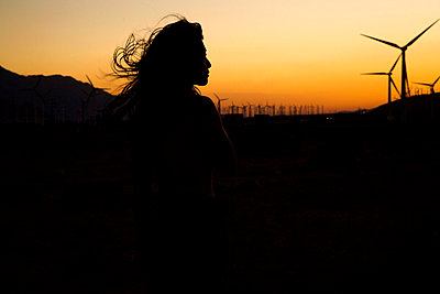 silhouette of woman in front of wind farm at sunset - p1166m2157060 by Cavan Images