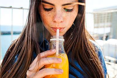 Young woman with freckles drinking orange juice - p300m1416516 by Valentina Barreto