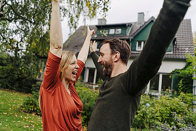 Proud home owners cheering in their garden - p300m2167321 by Kniel Synnatzschke