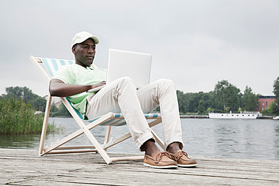 Man relaxing on deckchair with laptop by lake - p301m844123f by Paul Hudson