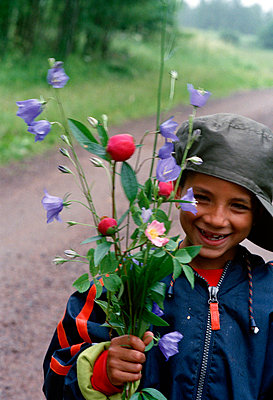 Smiling boy holding a bunch of flowers Smaland Sweden. - p5281134 by Athina Strataki