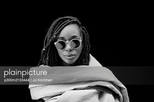 Portrait of woman with dreadlocks wrapped in blanket in front of black background - p300m2103444 by Jo Kirchherr