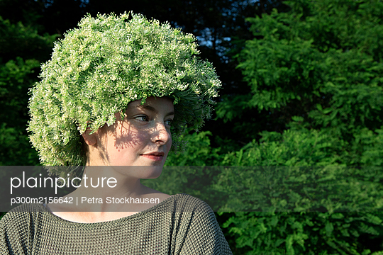 Portrait of young woman wearing headpiece of flowers - p300m2156642 by Petra Stockhausen