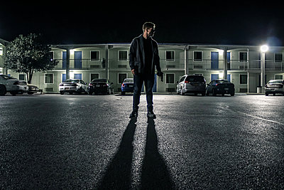 Man in a street at night - p1019m1424632 by Stephen Carroll