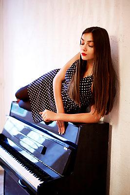 Junge Frau in gepunktetem Kleid auf dem Klavier - p1521m2129138 von Charlotte Zobel