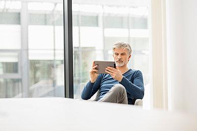 Mature man sitting in his office, using digital tablet - p300m1587171 von Jo Kirchherr