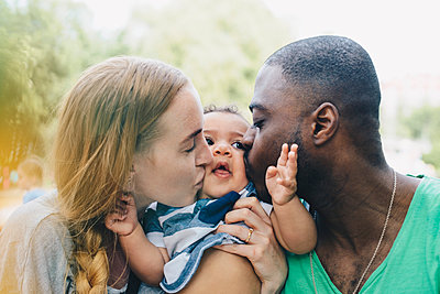 Close-up of multi-ethnic parents kissing son - p426m1507073 by Maskot