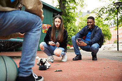 Friends controlling robot with smart phone while having battle at park - p426m2135413 by Maskot