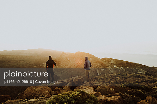 Two men stand on mountain top watching sunrise - p1166m2129910 by Cavan Images