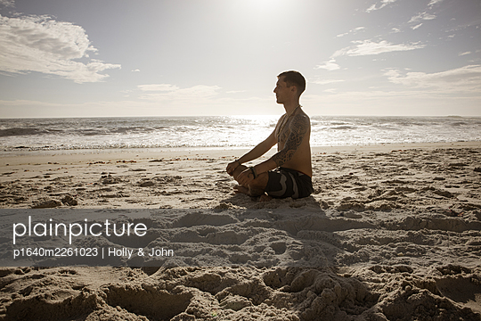 Man practises meditation on the beach in the sunshine - p1640m2261023 by Holly & John