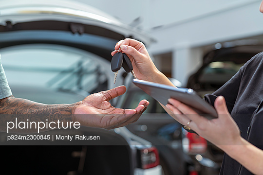 UK, Close-up of hands with car keys and digital tablet - p924m2300845 by Monty Rakusen