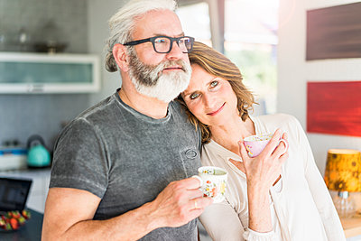 Mature couple drinking coffee in kitchen at home - p300m1568308 by Robijn Page