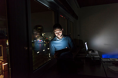 Businessman sitting on window sill in office at night using tablet - p300m1580729 by Uwe Umstätter