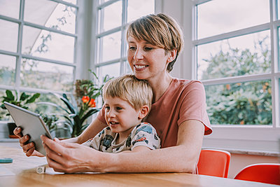 Mother using digital tablet with son while sitting at home - p300m2226255 by Mareen Fischinger