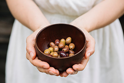 Woman holding bowl of olives, mid section - p429m1494210 by Alberto Bogo
