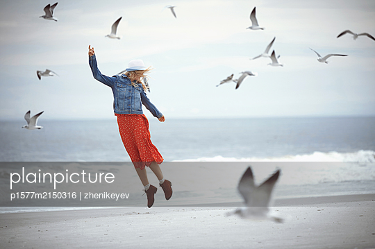Woman jumping next to the ocean surrounded by flying seagulls - p1577m2150316 by zhenikeyev