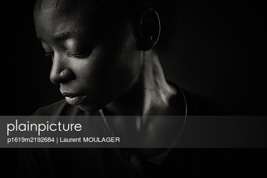 Portrait of a young black woman looking down - p1619m2192684 by Laurent MOULAGER