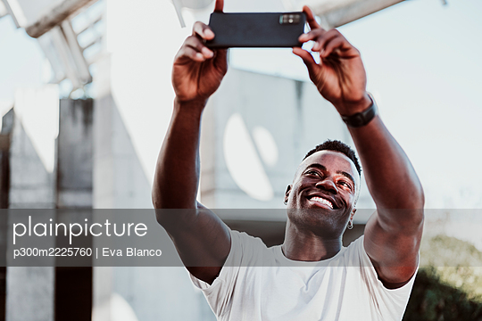 Smiling male athlete taking selfie on smart phone - p300m2225760 by Eva Blanco