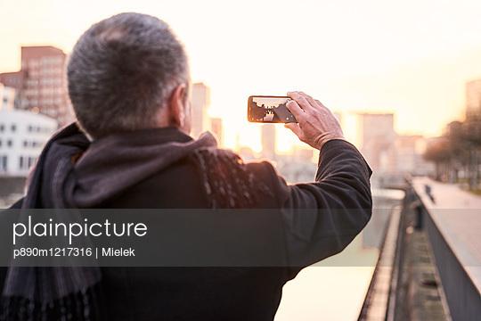 Mann fotografiert mit Smartphone - p890m1217316 von Mielek