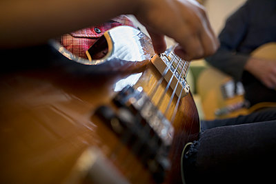 Close up musician strumming guitar - p1192m1493324 by Hero Images