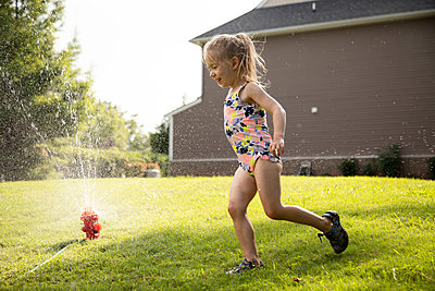 Portrait of a young girl playing in a backyard sprinkler - p1480m2148174 by Brian W. Downs